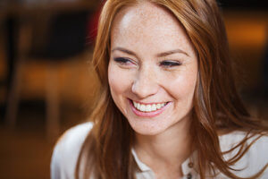 smiling woman with freckles has Veneers